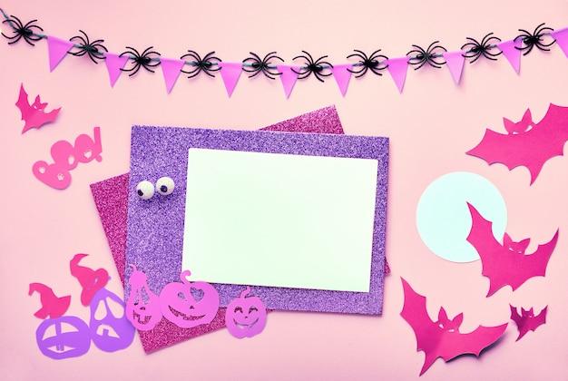 Kreativer halloween-flachtisch auf rosa papier mit kopierraum. leere karten- und papierdekorationen: fledermäuse und kürbislaterne