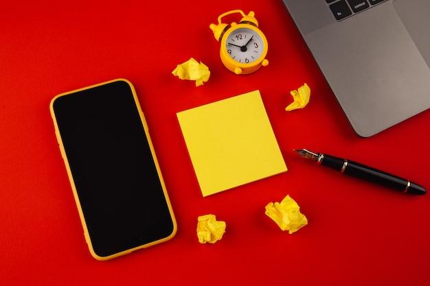 Kreativer heimarbeitsplatz mit schwarzem stift, uhr und gelber haftnotiz auf buntem