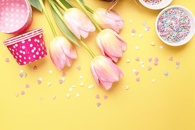 Kreativer hintergrund der osterferien mit osterkuchen, tulpen und dekorationen draufsicht flach lag mit kopierraum