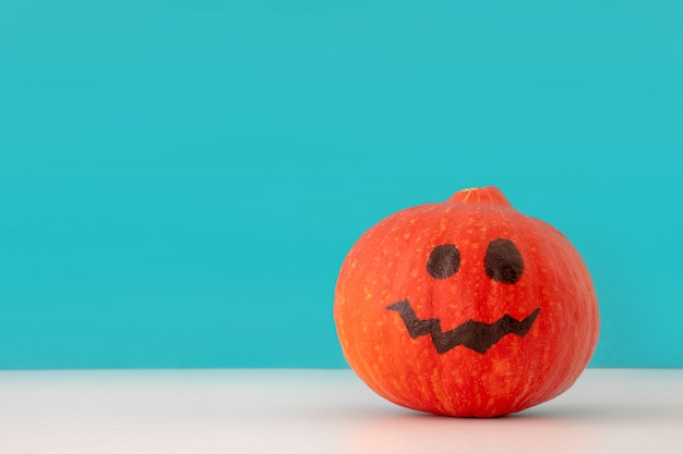 Kreativer hintergrund des halloween-feiertags mit laternenkürbis der steckfassung o auf blauem hintergrund