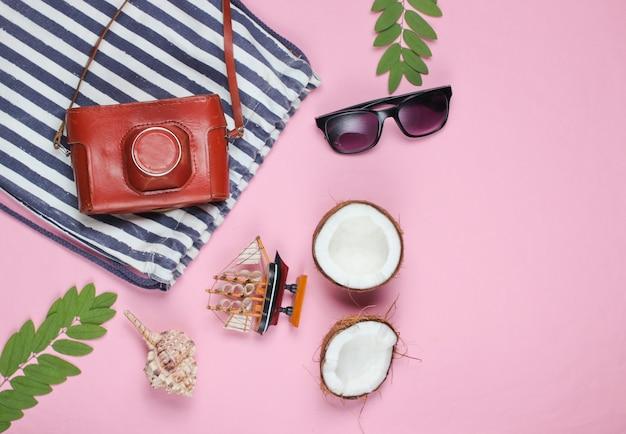 Kreativer hintergrund des sommers. gestreifte strandtasche, zubehör auf einem rosa hintergrund. draufsicht.