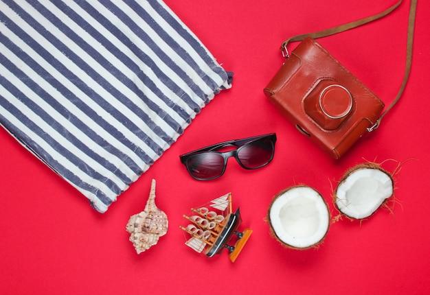 Kreativer hintergrund des sommers. strand gestreifte tasche, zubehör auf rotem hintergrund. draufsicht.