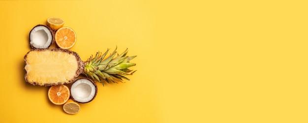 Kreativer hintergrund von tropischen früchten des sommers mit orange, zitrone, ananas auf einem gelben pastellhintergrund