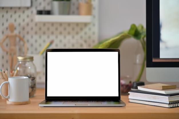 Kreativer hölzerner schreibtisch des modells mit laptop des leeren bildschirms