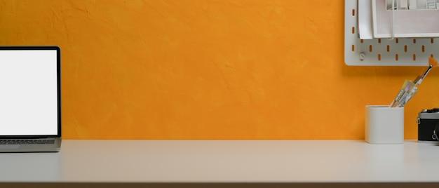 Kreativer home-office-schreibtisch mit kopierraum, laptop, malpinsel und regal auf gelber wand