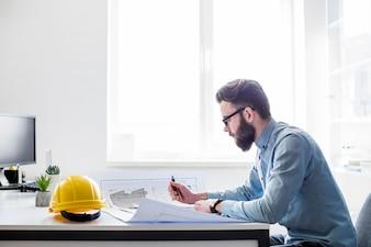 Kreativer Ingenieur, der an Bauplan am Arbeitsplatz arbeitet