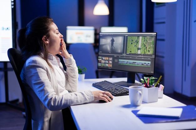Kreativer inhaltsersteller, der an der postproduktionsmontage arbeitet, um die frist einzuhalten, die am schreibtisch im start-up-geschäftsbüro sitzt