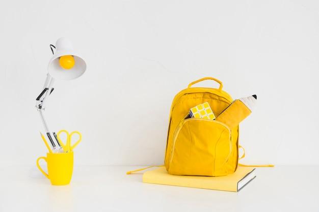 Kreativer jugendarbeitsplatz mit gelbem rucksack und rubiks würfel