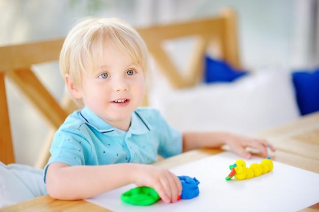 Kreativer junge, der mit buntem modellierton am kindergarten spielt