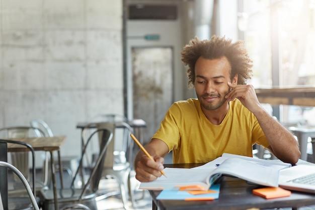 Kreativer junger autor mit lockigem haar und dunkler haut, die lässig gekleidet in der cafeteria sitzt und sich darauf vorbereitet, einen neuen artikel in seiner zeitung zu schreiben, mit einem sanften lächeln im gesicht und guten ideen