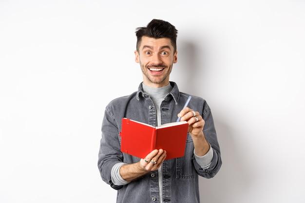 Kreativer junger mann, der aufgeregt lächelt, während er notizen macht, ideen im planer aufschreibt, rotes tagebuch hält und glücklich schaut, gegen weißen hintergrund stehend.