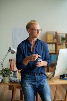 Kreativer kaukasischer mann, der vor schreibtisch im büro steht, schale hält und weg schaut