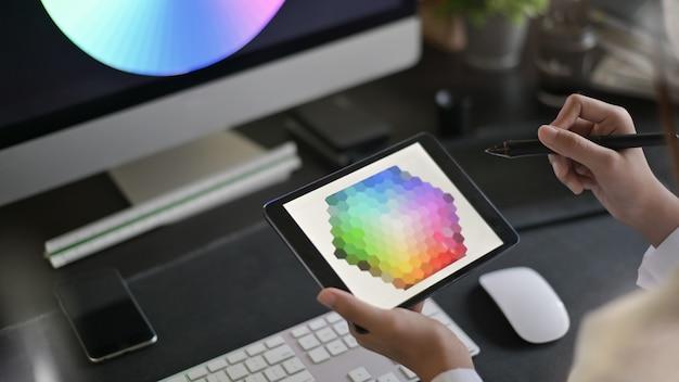 Kreativer künstler des webdesigns mit dem arbeiten an farbauswahl auf grafischer tablette.