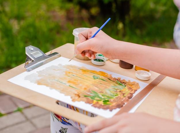 Kreativer künstler malt ein buntes bild. nahaufnahme von händen und von bürste bei draußen malen