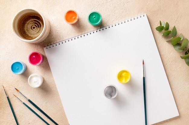 Kreativer künstlerarbeitsplatz mit skizzenbuchpinseln malen dosen