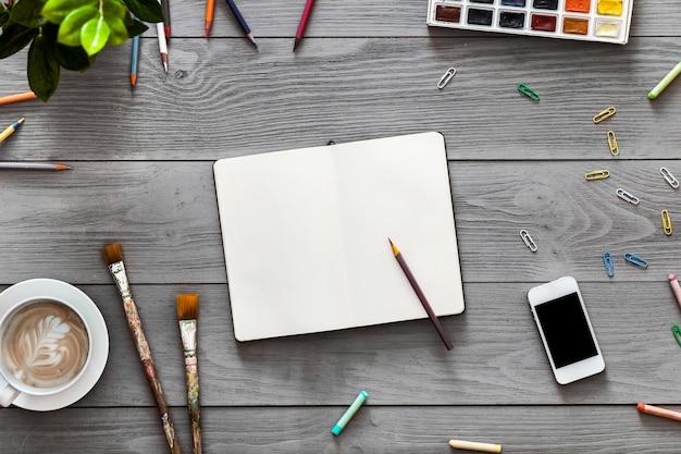 Kreativer kunsttisch mit leeren notizbuchstiftfarben liefert für arbeitsskizzen