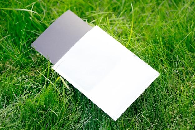 Kreativer layout-kompositionsrahmen aus grün-grünem rasen mit schwarz-weißem etui für tags, markenzubehör, flacher lay- und kopierraum
