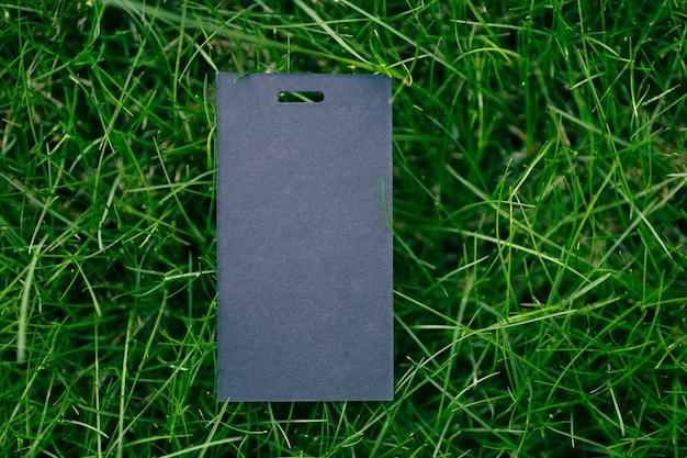 Kreativer layout-zusammensetzungsrahmen aus grünem grasrasen mit einem schwarzen preisschild für kleidung für die fabrikflachlage und kopienraum für das logo.