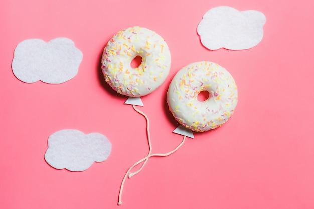 Kreativer lebensmittel-minimalismus, donut in form des ballons im himmel mit wolkenhintergrund