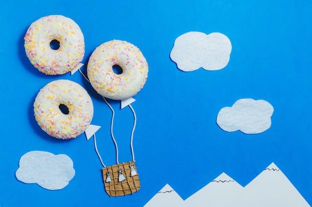 Kreativer lebensmittelminimalismus, donut in form von aerostat im blauen himmel mit wolken