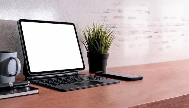 Kreativer loft-arbeitsbereich mit tablett mit leerem bildschirm und magischer tastatur auf holztisch mit kopierraum.