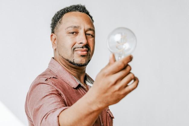 Kreativer mann, der eine glühbirne hält