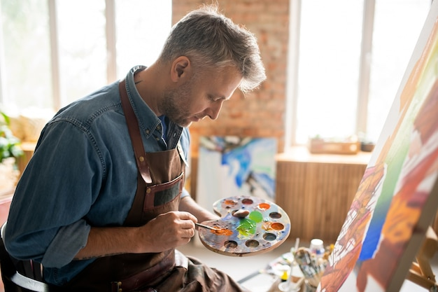 Kreativer mann in der schürze, die farben auf palette mischt, während über neues gemälde vor staffelei im studio arbeitet