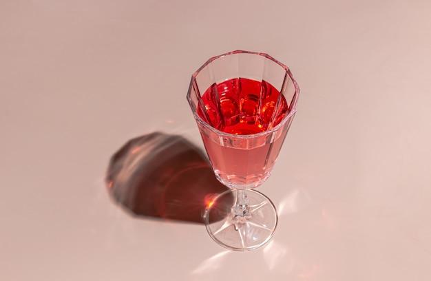 Kreativer minimalistischer pastellrosa partyhintergrund mit einem glas rosé-champagner
