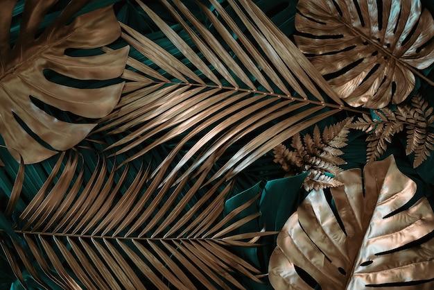Kreativer naturhintergrund gold und grüne tropische monstera und palmblätter minimale sommerabstra