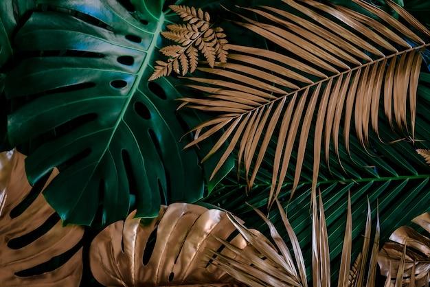 Kreativer naturhintergrund gold und grüne tropische monstera und palmblätter minimale sommerabstraktion
