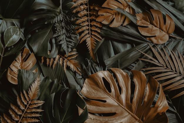 Kreativer naturhintergrund gold und grüne tropische monstera und palmblätter