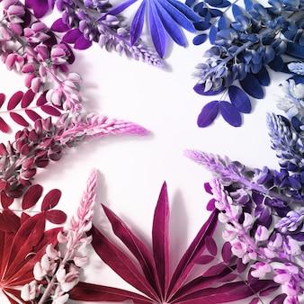Kreativer naturrahmen gemacht von den tropischen blättern und von den blumen in den tendenzsteigungsfarben.