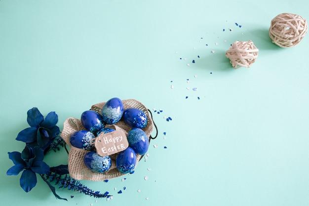 Kreativer osterhintergrund mit trendblauen eiern.