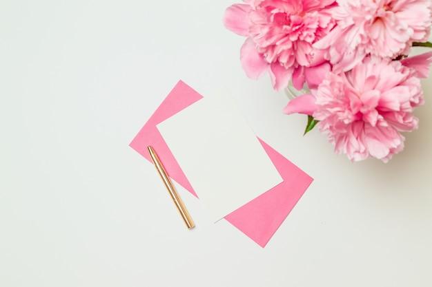 Kreativer plan gemacht vom rosa papierumschlag mit einem goldstift, ein blumenstrauß von den rosa pfingstrosen lokalisiert auf weiß