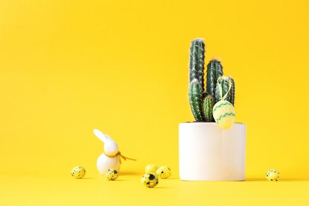 Kreativer plan ostern-hintergrund. kaktus mit bunten eiern