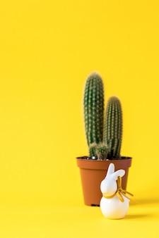 Kreativer plan ostern-hintergrund. kaktus mit und kaninchen