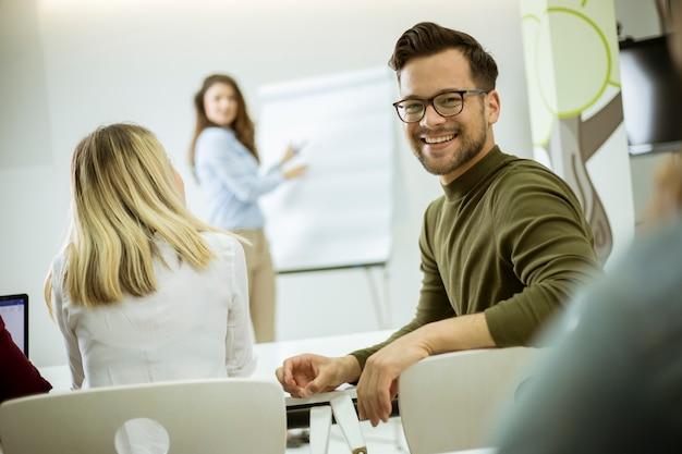 Kreativer positiver weiblicher führer, der über unternehmensplan mit studenten während der werkstatt spricht