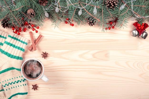 Kreativer rahmen aus weihnachtstannenzweigen auf weißem holz mit roten dekorationskegeln.