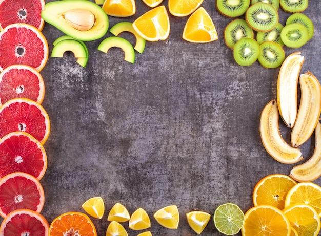 Kreativer rahmen mit draufsichtpampelmusenavocadokiwibanane der frischen köstlichen zitrusfrüchte orange zitrone mit kopienraum