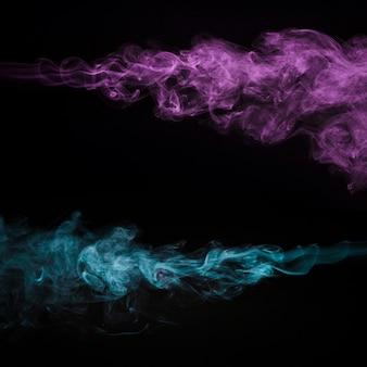 Kreativer rosafarbener und blauer rauch auf schwarzem hintergrund