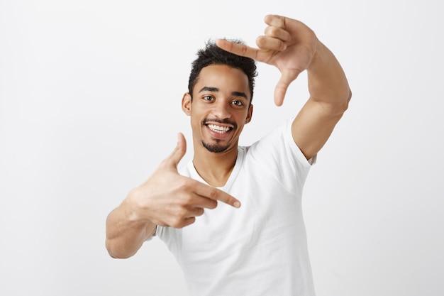 Kreativer schöner afroamerikanermann, der durch handrahmen schaut und lächelnden, bildenden moment darstellt