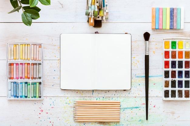 Kreativer schreibtisch mit pinseln auf weißem holzhintergrund