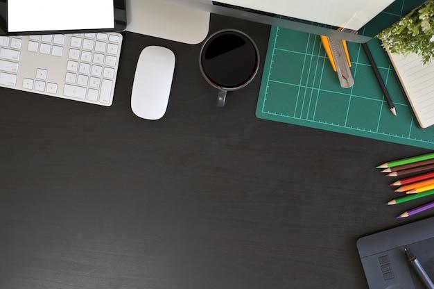 Kreativer schreibtischarbeitsplatz mit modelltablet-computer und büroausstattung auf schwarzer tabelle, draufsicht.