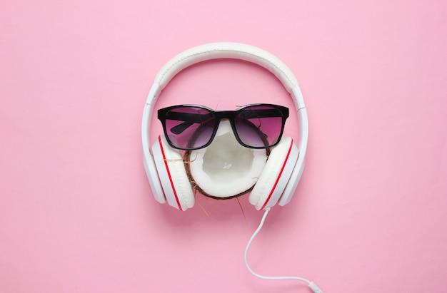 Kreativer sommer-minimalismus. kokosnuss, sonnenbrille, kopfhörer auf rosa pastellhintergrund. draufsicht
