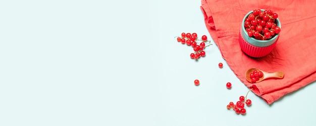 Kreativer sommer von roten reifen johannisbeeren in einer blauen schale und mit einem hölzernen löffel auf einem blauen hintergrund