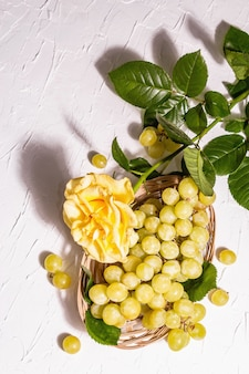 Kreativer sommerhintergrund. gelbe rose, weiße traube, weidenkorb. ein trendiges hartes licht, dunkler schatten, draufsicht