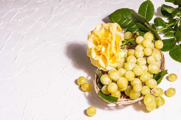 Kreativer sommerhintergrund. gelbe rose, weiße traube, weidenkorb. ein trendiges hartes licht, dunkler schatten, kopierraum