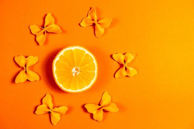 Kreativer sommerplan gemacht von den orangen und von farbigem teigwarengrieß papillon auf orange hintergrund