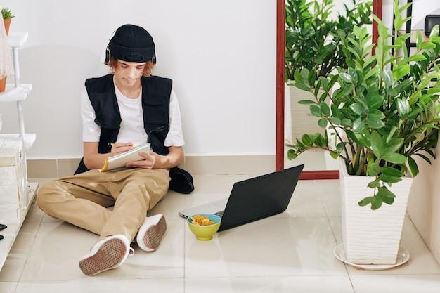 Kreativer teenager-blogger in kopfhörern, der mit geöffnetem laptop auf dem boden sitzt und szenario für sein bevorstehendes video im notizbuch schreibt