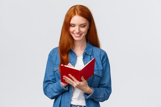 Kreativer und begabter schöner weiblicher student bereiten zeitplan für morgenklassen vor und schreiben in das tagebuch und machen kenntnisse im fantastischen notizbuch und stehen weiß